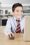 在膝上型计算机的孩子在家 免版税库存图片