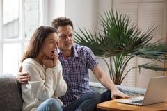 在膝上型计算机的害怕的人拥抱震惊妇女观看的恐怖片 免版税库存照片