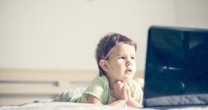 在膝上型计算机的小女孩观看的动画片,当说谎在床上时 库存图片