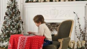 在膝上型计算机的小男孩观看的圣诞节电影在家 库存图片