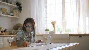 在膝上型计算机的年轻女性自由职业者ig玻璃工作和采取笔记在明亮的厨房里 影视素材