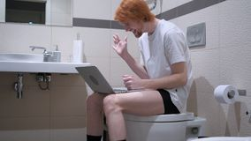 在膝上型计算机的录影闲谈由人坐洗手间洗脸台 库存图片