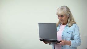 在膝上型计算机的惊奇的年长女性读的消息,喜讯,通信 影视素材