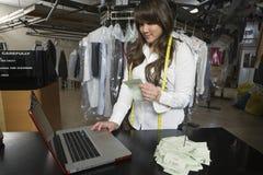在膝上型计算机的所有者计算的数额在洗衣店柜台 免版税库存图片