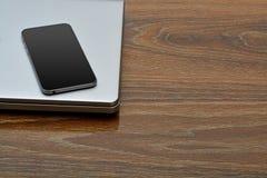 在膝上型计算机的智能手机有木背景 图库摄影