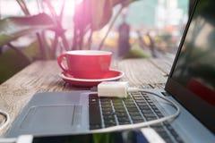 在膝上型计算机的流动充电的插座有红色咖啡的,断裂时间 库存照片