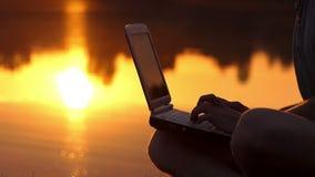 在膝上型计算机的男性手指类型室外在湖岸在晚上 股票视频