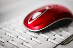 在膝上型计算机的白色键盘的一只美丽的红色无线老鼠 免版税库存图片