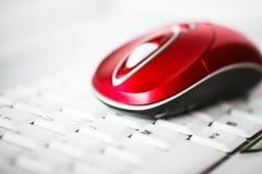 在膝上型计算机的白色键盘的一只美丽的红色无线老鼠 免版税图库摄影