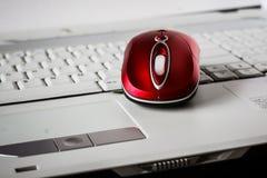 在膝上型计算机的白色键盘的一只美丽的红色无线老鼠 图库摄影