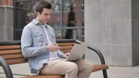 在膝上型计算机的网上视频聊天由年轻人坐长凳