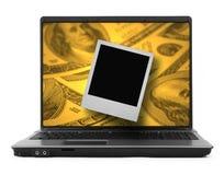 在膝上型计算机的美元和照片 免版税库存图片
