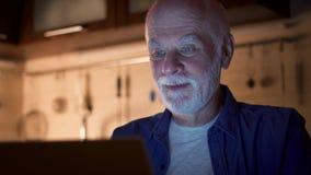 在膝上型计算机的老人工作从家庭办公室在晚上 商人知道愉快好的消息激动和 股票视频
