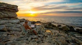 在膝上型计算机的自由职业者工作在deauty日落backgrou的海岸海 免版税库存图片