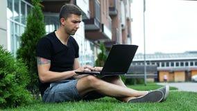 在膝上型计算机的自由职业者工作露天,当坐草时 股票录像