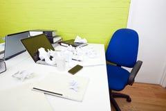 在膝上型计算机的被弄皱的纸在有空的椅子和文件夹的书桌上 免版税库存照片