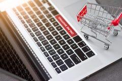在膝上型计算机的购物车台车有文本网上购物的 免版税库存图片
