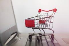 在膝上型计算机的购物车 网上购物和电子商务概念 图库摄影