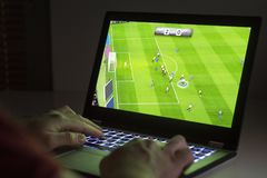 在膝上型计算机的足球或橄榄球电子游戏 年轻人使用 图库摄影