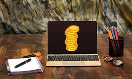 在膝上型计算机的金币筛选网上收入概念 库存照片