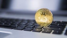 在膝上型计算机的金黄bitcoin 在计算机黑色键盘的Bitcoin隐藏货币 数字式货币 虚拟的货币 金属 免版税图库摄影