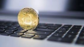 在膝上型计算机的金黄bitcoin 在计算机黑色键盘的Bitcoin隐藏货币 数字式货币 虚拟的货币 金属 免版税库存照片