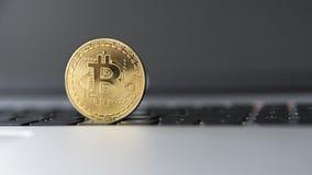 在膝上型计算机的金黄bitcoin 在计算机黑色键盘的Bitcoin隐藏货币 数字式货币 虚拟的货币 金属 免版税库存图片