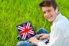 在膝上型计算机的青少年的学习的英语户外。 免版税库存照片