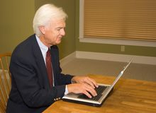 在膝上型计算机的高级生意人 库存照片