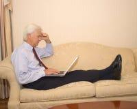 在膝上型计算机的高级生意人 免版税库存照片