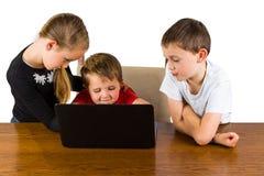 在膝上型计算机的3个孩子 免版税库存图片