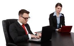 在膝上型计算机的年轻企业夫妇 库存图片