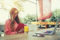在膝上型计算机的年轻创造性的妇女工作,当食用在大阳台时的早餐 库存照片