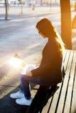 在膝上型计算机的年轻学生读书消息在沿海岸区的日落 免版税库存照片