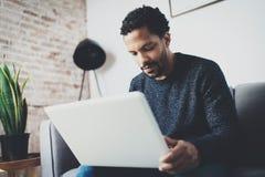 在膝上型计算机的年轻非洲人文字电子邮件,当坐沙发在他的现代coworking的演播室时 概念的充分 免版税库存图片