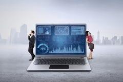 在膝上型计算机的Businessteam倾斜 免版税库存图片