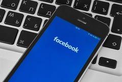 在膝上型计算机的IPhone 5s有对Facebook的流动申请的 库存图片