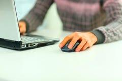 在膝上型计算机老鼠和键盘的男性手在键入期间的 免版税库存照片