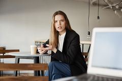 在膝上型计算机能您投入您的面孔和没有与我,感谢谈话 坐在咖啡馆的懊恼恼怒的妇女画象,举行 免版税库存照片