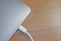 在膝上型计算机膝上型计算机和缆绳` s白色的USB类型C口岸  图库摄影