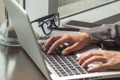 在膝上型计算机键入年轻女人的特写镜头图象 免版税图库摄影