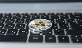 在膝上型计算机键盘特写镜头的银色金波纹硬币 Blockchain采矿 数字式金钱和真正cryptocurrency 库存图片