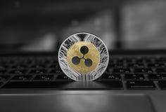 在膝上型计算机键盘特写镜头的银色金波纹硬币 Blockchain采矿 数字式金钱和真正cryptocurrency 免版税库存图片