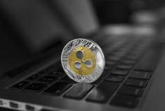 在膝上型计算机键盘特写镜头的银色金波纹硬币 Blockchain采矿 数字式金钱和真正cryptocurrency 免版税库存照片