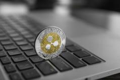 在膝上型计算机键盘特写镜头的银色金波纹硬币 Blockchain采矿 数字式金钱和真正cryptocurrency 库存照片