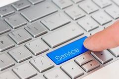 在膝上型计算机键盘的一个手指新闻蓝色服务按钮 免版税库存照片