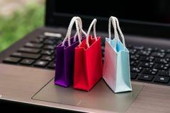 在膝上型计算机键盘的三个五颜六色的纸购物袋 想法土佬 免版税库存图片