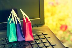 在膝上型计算机键盘的三个五颜六色的纸购物袋 想法土佬 图库摄影