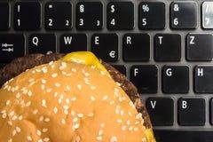 在膝上型计算机键盘的乳酪汉堡-快餐午餐在工作场所 库存照片