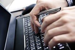 在膝上型计算机键盘的商人手 库存图片